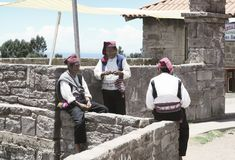 Three men dressed in traditional outfits specific for the Taquile Island region, one of them knitting a hat Royalty Free Stock Image