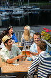 Three men drinking beer at terrace bar Stock Photo