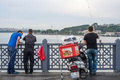 Three Men Fishing wiht Three Rods on Galata Bridge in Early Morn Royalty Free Stock Photos