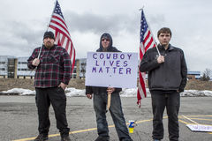 Three men with flags and signs. Stock Photos
