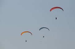 Three men flying on a red paraglider it the evening Royalty Free Stock Image