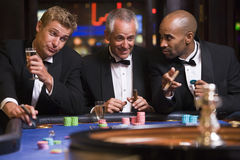 Three men gambling at roulette table Stock Photo