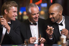 Three men gambling at roulette table Stock Images