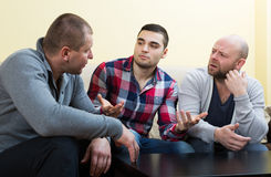 Three men  at home. Three men having a serious conversation at home Stock Photography