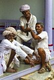 Three Hindu men spend their time sitting in the doorway of the house.
