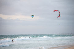 Three men kitesurfing on the beach in Indian ocean in Perth Stock Images
