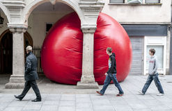 Three men look at Kurt Perschke's giant Red Ball Stock Image