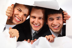 Three men looking out in hole in paper royalty free stock images