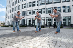 Three men with a mobile phone in front of a white business cente Royalty Free Stock Images