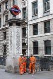Three men in orange work outfit near entrance to underground sta Royalty Free Stock Photo