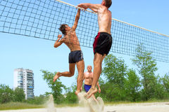 Three men play beach - fight Stock Images