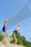 Three men play beach volley Stock Image