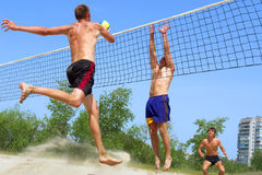 Three men play beach volley. Three men, clumsy, fat and handsome, play beach volleyball (focus on second closest one). Shot near Dnieper river, Ukraine Stock Photos