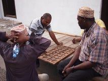 Three men play Zanzibar board game Royalty Free Stock Image