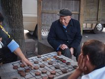 Three Men Playing Chinese Chess. Fenghuang, China - 17 October, 2016: Three elderly men playing Xiangqi, chinese chess Royalty Free Stock Images
