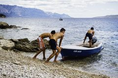 Three Men Pushing Speed Boat on Seashore Royalty Free Stock Photo