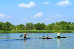 Three men row in boats Royalty Free Stock Image