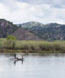 Three Men in a Rowboat. Two men fishing and a third rowing the boat on the Missouri River in Montana. All have backs to the camera. The river bank is lined with stock images