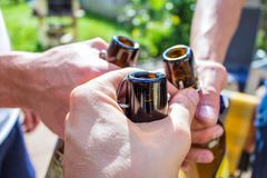 Three men`s hands holding brown beer bottles in summer on a barbecue stock image