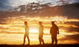 Three men silhouettes with different body types on a sunset sky. Body shape transformation and healthcare. 3D illustration stock images