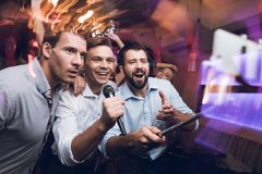 Three men sing at a karaoke club. Young people have fun in a nightclub. They are very cheerful and they smile. Stock Image