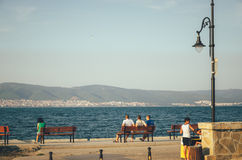 Three men sit on a bench on the promenade of Nessebar and look at the Sunny Beach. Stock Image