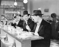 Three men sitting at the counter of a diner Stock Images