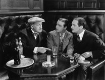 Three men sitting together at a bar Stock Photography