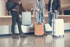 Male friends locating with baggages in airport. Three men situating near luggages while waiting for plane in hall. Expectation and tourism concept Stock Photos
