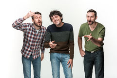 The three men are smiling, looking at camera Royalty Free Stock Image