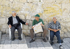 Three Men in Street, Jerusalem. Old City, Jerusalem, Israel - June 9, 2007: Three senior men sit on the steps of Casa Nova Road in the Christian Quarter of the royalty free stock photo