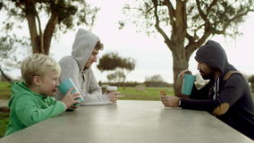 Three men at the table outdoors. Two adults with hoods on their heads and one boy are sitting at the table outdoors and having a nice talk stock video