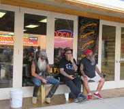 Three men at tattoo shop during Sturgis, SD 77th Rally. Sturgis, South Dakota during the 77th Annual Motorcycle Rally in August 2017. Three older men with long stock image