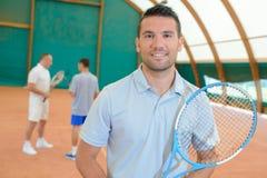 Three men in tennis court royalty free stock photos