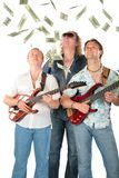 Three  men with two guitars look on falling dollar Royalty Free Stock Photo
