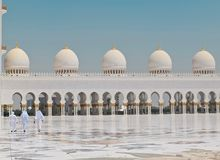 Three Men Walking in Front of a Dome Building Royalty Free Stock Image