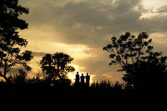 Three Men Walking in Sunset Sky. Silhouette of three men walking in the evening sky Among the Forest Stock Photography