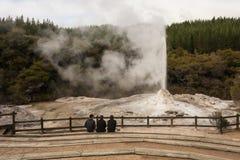 Three men watching Lady Knox geyser Stock Photo