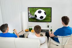 Three men watching soccer match. Rear View Of Three Men Sitting On Couch Watching Football Match On Television Stock Image