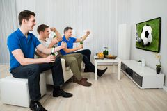 Three men watching soccer match. Side View Of Three Men Sitting On Couch Watching Football Match On Television Stock Images
