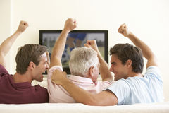 Three Men Watching Widescreen TV At Home Royalty Free Stock Photo