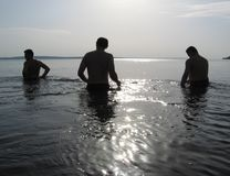 Three men on the water Stock Photo