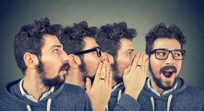 Three men whispering each other and to shocked astonished guy in the ear. Word of mouth. stock photo