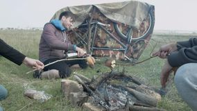 Three men in the wild fry bread on sticks and drink tea from a thermos. stock video footage