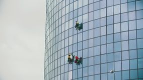 Three men workers hanging on ropes and cleaning the exterior glass windows of a business skyscraper after rain - autumn