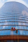 Three men workers in red and dark work clothes cleaning the exterior