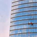 Three men workers in red and dark work clothes cleaning the exterior windows of a business skyscraper, bottom view
