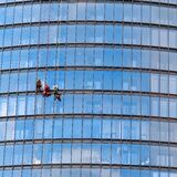 Three men workers in red and dark work clothes cleaning the exterior windows of a business skyscraper