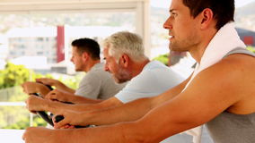 Three men working out on exercise bikes Stock Image