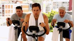 Three men working out on exercise bikes Royalty Free Stock Photos